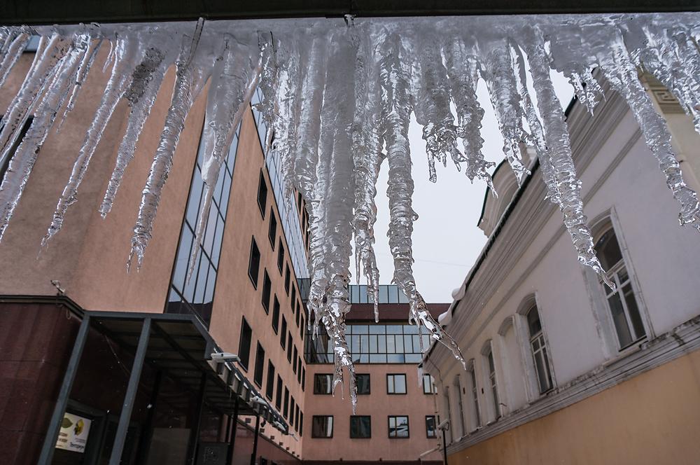 В центре города вновь счищают снег с крыш на головы прохожих