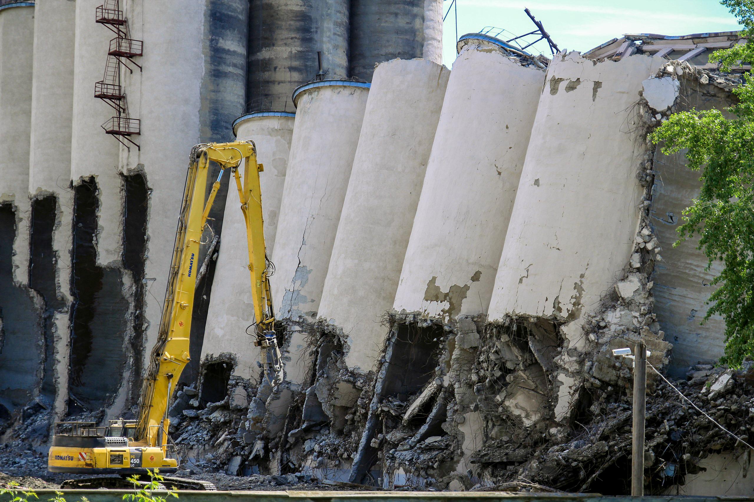 Упавший элеватор доламывает строительная техника