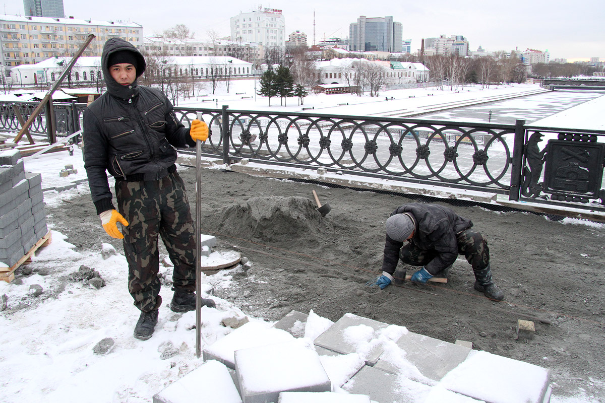 На Плотинке рабочие бодро укладывают плитку на свежий снег